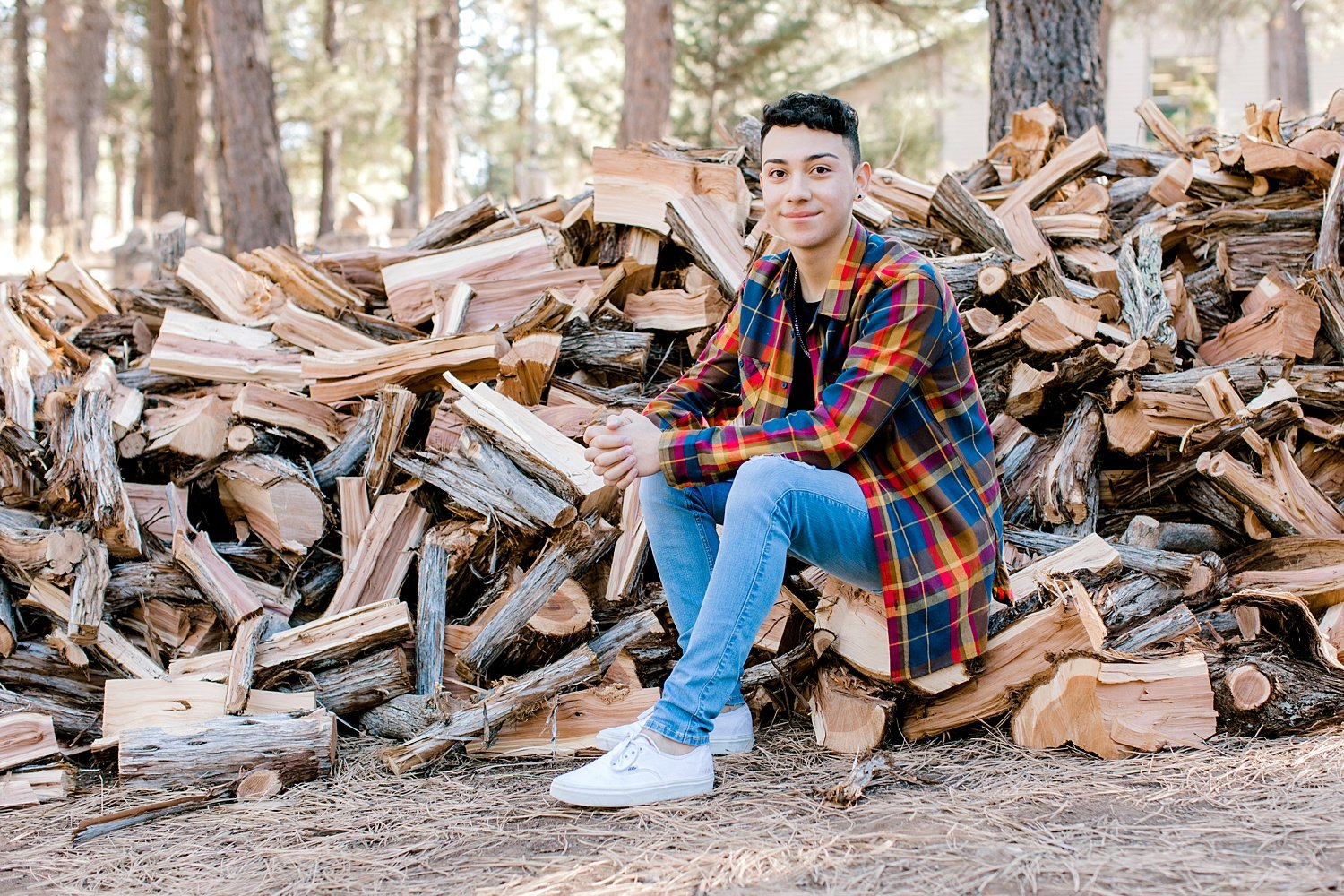 Guy in a flannel shirt sitting in a chopped wood pile in Flagstaff, Arizona